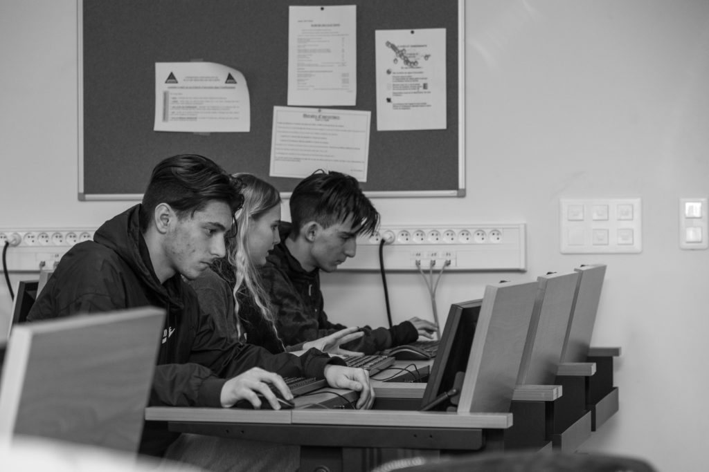 Trois personnes sont sur des ordinateurs