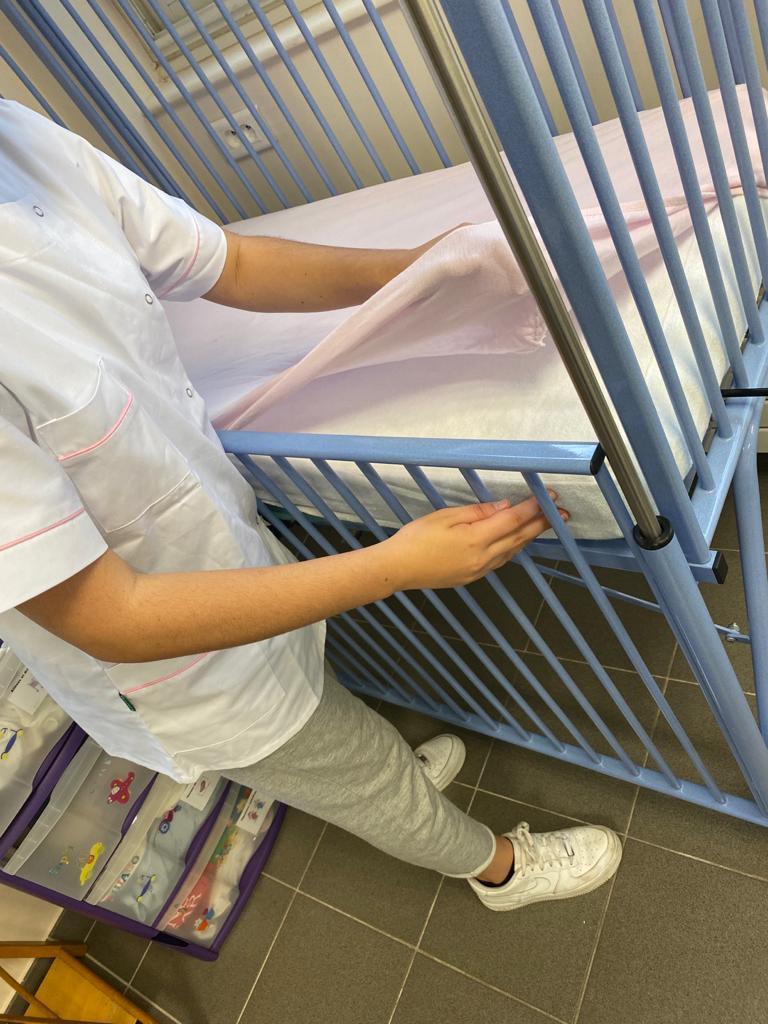 Une élève refait la literie d'un lit de crèche