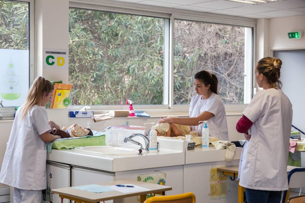 Des élèves effectuent des changes sur des poupons sous la surveillance d'un professeur